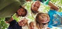 5 Kinder im Kreis stehend, lachend nach unten schauend